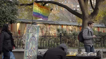 rainbow flag for LGBT peace - gay colors at Union Square with diverse variety of people walking by in slow motion