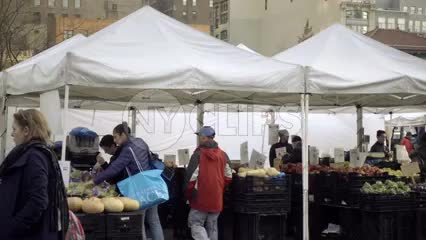Union Square Park Farmers Market in winter with people buying and selling produce and food under tents