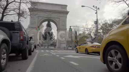 low angle of Washington Square Park on cloudy winter day with Christmas tree underneath arch, taxi cabs driving by