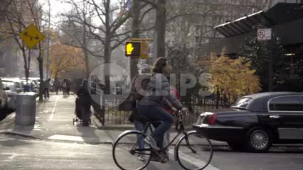 man on bicycle riding down Mercer Street past stretch limousine on street
