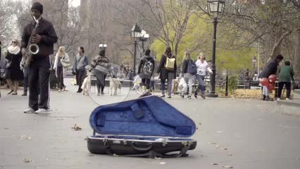 musician playing saxophone in Washington Square Park with open sax case for donations
