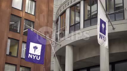 NYU flags panning to Stern School of Business building - students entering and exiting
