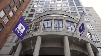 NYU flags tilting down to Stern School of Business building circular entrance