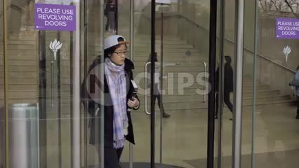 NYU revolving door, student exiting New York University building