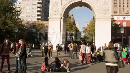 people walking through arch on sunny day - playing and having fun in Washington Square Park in summer