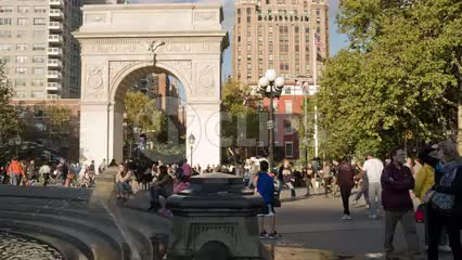 famous arch in Washington Square Park on bright sunny day - crowded with people playing frisbee in summer