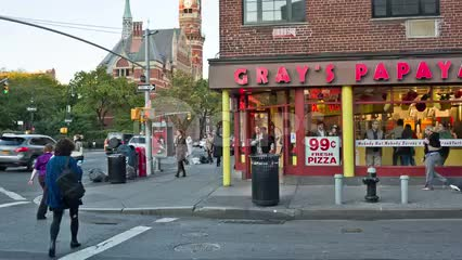 famous Gray's Papaya on 8th Street in Greenwich Village with Jefferson Market block tower on 6th Ave