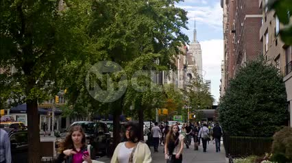 windy early summer day on Lower 5th Ave with NYU students walking - people enjoy end of spring - Empire State Building street view