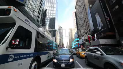 bus and cars driving through Times Square traffic on summer day