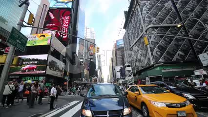 cars and taxi cab driving in traffic through Times Square during the day