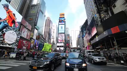 cars driving in Times Square traffic on bright sunny day with blue sky and clouds