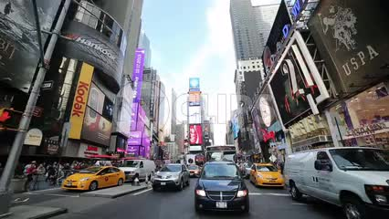 cars in Times Square traffic driving through crosswalk in wide shot