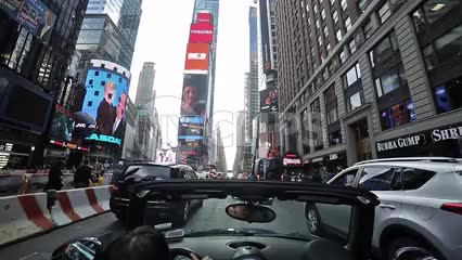 woman in convertible driving through Times Square on cloudy summer day