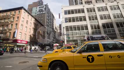 taxis driving in Midtown traffic on sunny day