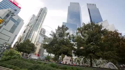 driving around Columbus Circle center fountain in summer with skyscrapers towering over trees