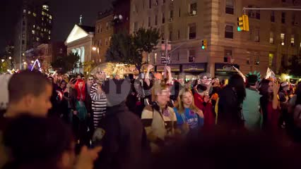 monsters and goblins and ghouls in costumes marching in Halloween parade in Greenwich Village on 6th Ave