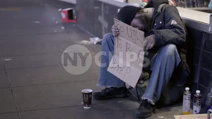 homeless man sleeping with sign in hand on street at night