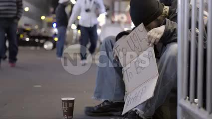 homeless man holding sign at night on street off Times Square on sold fall night
