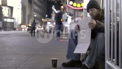 tragic homeless man with humorous sign in Times Square at night