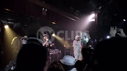 far shot of Mobb Deep rapping at live show - zooming into stage from crowd in slow motion