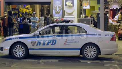 NYPD police car parked outside store in summer with people hanging out