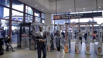 people entering Times Square subway station at night with turnstiles