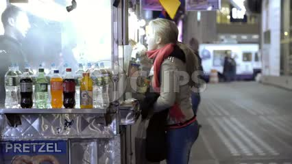 woman buying hot dog at food cart vendor on street at night in fall