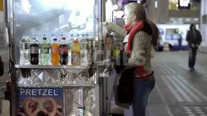 woman buying pretzel at food truck street vendor at night in NYC