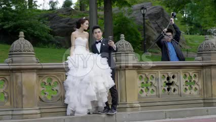 photographer setting up tripod in Central Park for wedding of beautiful couple