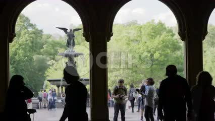 silhouettes under Bethesda Terrace - view of angel statue with wings and water fountain in summer - photographer setting up shot with DSLR camera