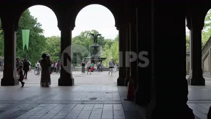 silhouette of family under Bethesda Terrace in Central Park with statue in background