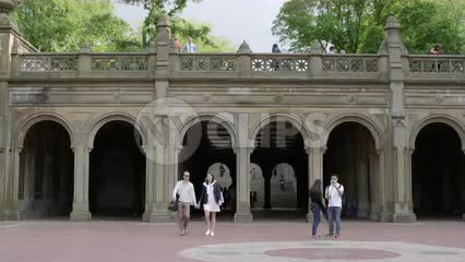 couple holding hands in summer walking from Bethesda Terrace arches in Central Park