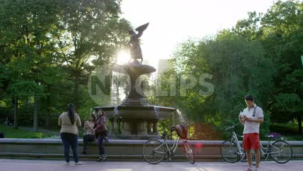 lost tourist with map - man in shorts and girls at Bethesda statue in Central Park on sunny day in summer