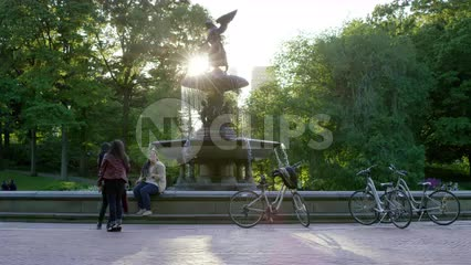 girls hanging out in Central Park by Bethesda statue with bicycles parked, leaning on circle