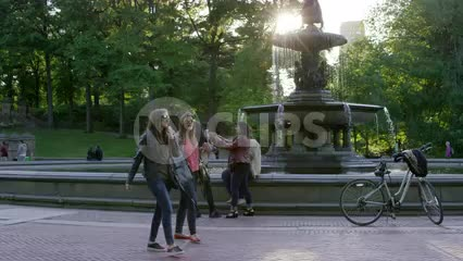 women walking by Bethesda statue and bicycles on sunny Central Park day in summer