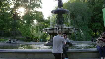 young man taking photograph of tourists, people with smartphone camera in Central Park in front of Bethesda statue