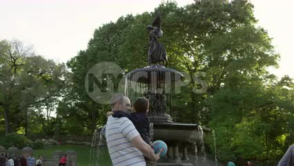father holding son in Central Park looking at Bethesda angel statue with wings and fountain with water in summer