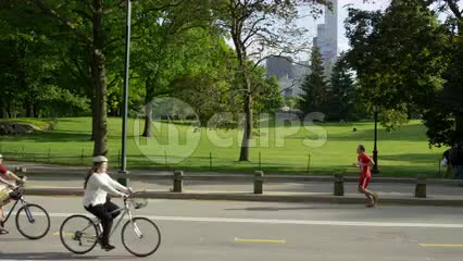 women on bicycles and man and woman jogging in Central Park on beautiful sunny summer day