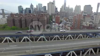 aerial over Manhattan Bridge with cars driving across to Brooklyn on spring day