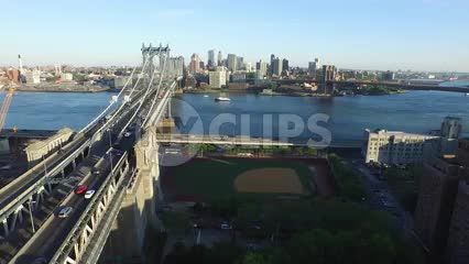 aerial pulling back from Manhattan Bridge on bright sunny day with baseball field on Eastside
