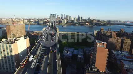 aerial moving toward Manhattan Bridge and East River - cars driving across to Brooklyn