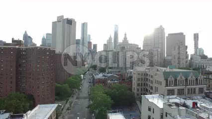 aerial view backing up from Manhattan skyscrapers to Chinatown buildings, cars on street downtown