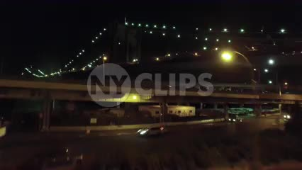 aerial of cars driving on FDR Drive and Brooklyn Bridge at night
