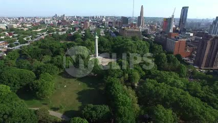 moving in aerial shot of Prison Ships Martyrs' Monument at Fort Greene Park in Brooklyn with trees on sunny day