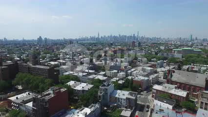 aerial of Brooklyn neighborhood with Manhattan skyline in background during day - rising shot