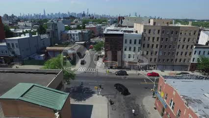 aerial rising up above Brooklyn neighborhood with Manhattan skyline in far distance in NYC