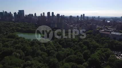 Central Park over trees and pond with skyscrapers in distance Manhattan NYC