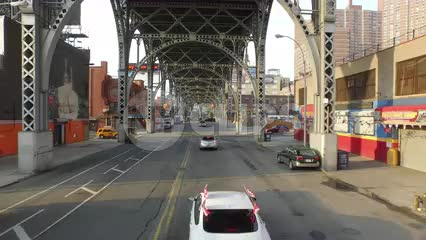 street in Harlem with cars driving under elevated subway train track on sunny day in NYC