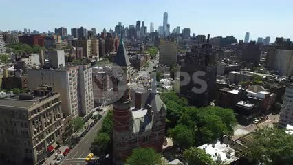 aerial of Jefferson Market Library clock tower in Greenwich Village backing up with Manhattan skyline skyscrapers in background in NYC