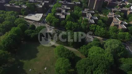 aerial of projects and trees and highway with Manhattan skyline in distance in NYC